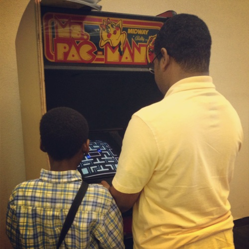 A son and his father and Ms. Pac Man. In a library. Together. Sharing and enjoying. So awesome.